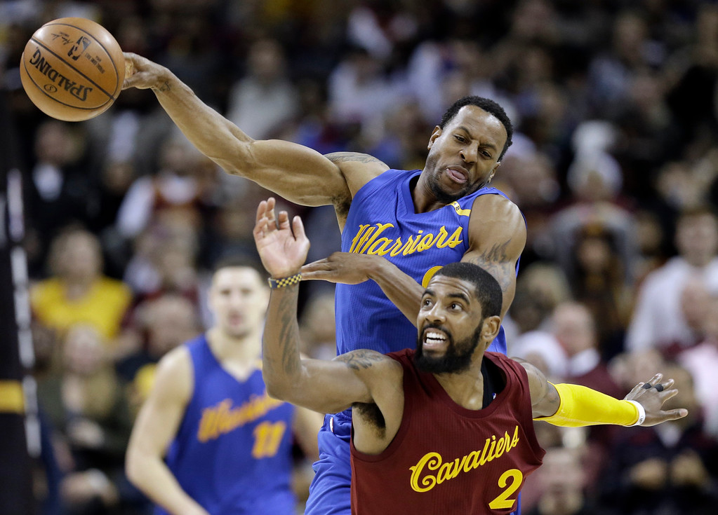 . Cleveland Cavaliers\' Kyrie Irving (2) and Golden State Warriors\' Andre Iguodala (9) battle for a loose ball in the second half of an NBA basketball game, Sunday, Dec. 25, 2016, in Cleveland. The Cavaliers won 109-108. (AP Photo/Tony Dejak)