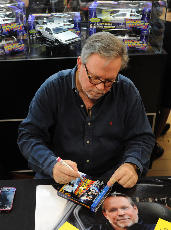 ". (John Valenzuela/Staff Photographer)  Kevin Pike, supervising the special effects on ""Back to the Future\"" and the creation of the iconic DeLorean Time Machine, autographs a copy of the movie for fan at Super Bad Action Figures in Redlands, Saturday, September 14, 2013."
