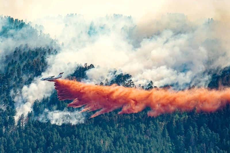 Air Tanker 161, an RJ-85, drops retardant on the Crow Peak Fire near Spearfish, South Dakota June 27, 2016.