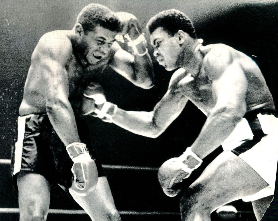 . PUNISHMENT FOR THE CHALLENGER--Heavyweight challenger Floyd Patterson takes a smash to the midsection as champion Cassius Clay throws full leverage into the blow in the 10th round of last night\'s title fight.  Patterson took a severe beating and lost on a 12th round technical knockout. (AP Wirephoto) 1965 But the blows didn\'t always go to the head.  The battered Patterson tries to pull in his belly to take some of the impact off Clay\'s solid right to the midsection during a 10th-round flurry.  By this time Clay was making a punching bag of the challenger. Credit: AP