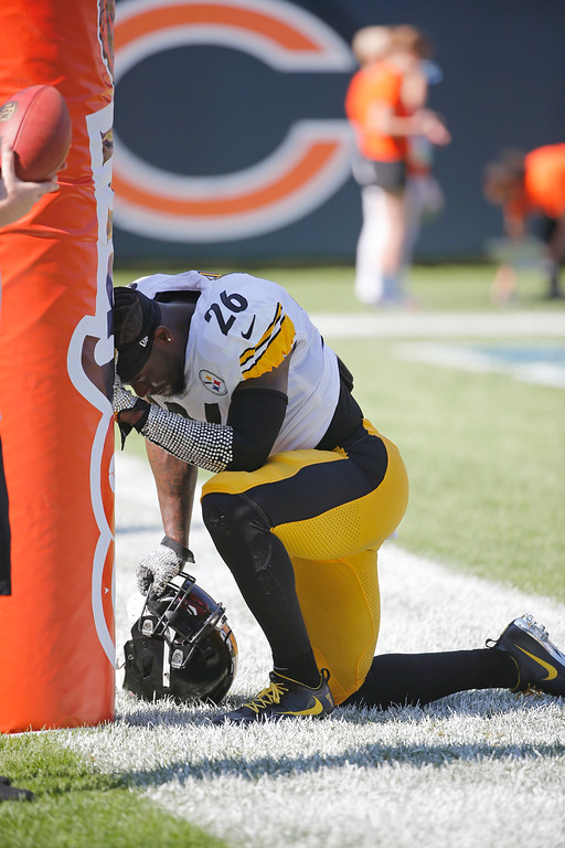 . Pittsburgh Steelers running back Le\'Veon Bell (26) kneels by the goal post before an NFL football game against the Chicago Bears, Sunday, Sept. 24, 2017, in Chicago. (AP Photo/Charles Rex Arbogast)