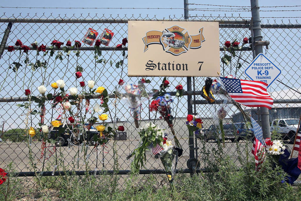 """. A memorial of flowers and flags forms outside of the Granite Mountain Hotshot Fire Station 7 in Prescott, Arizona July 1, 2013.  Reinforcements poured in Monday to battle a runaway wildfire which quadrupled in size overnight after killing 19 firefighters in one of the worst such incidents in US history. The Yarnell Hill fire -- which killed all but one member of a 20-strong \""""hotshot\"""" team -- was the biggest loss of firefighters\' lives since the September 11 attacks, and the most from a US wildfire in 80 years.   Krista Kennell/AFP/Getty Images"""