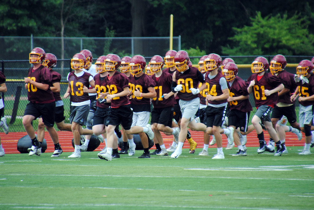 . Jon Behm - The Morning Journal<br> The Shoremen run a lap before the start of Avon Lake\'s first day of football practice on July 30.