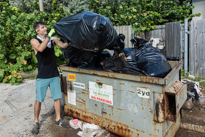 David Plotkin of West Palm Beach tosses a large bag of trash into a dumpster at the Currie Park Marina in West Palm Beach, Sunday, October 11, 2020. Plotkin, along with a group of volunteers is doing their part to clean up to try and clean up the pervasive litter problem in West Palm Beach. (JOSEPH FORZANO / THE PALM BEACH POST)