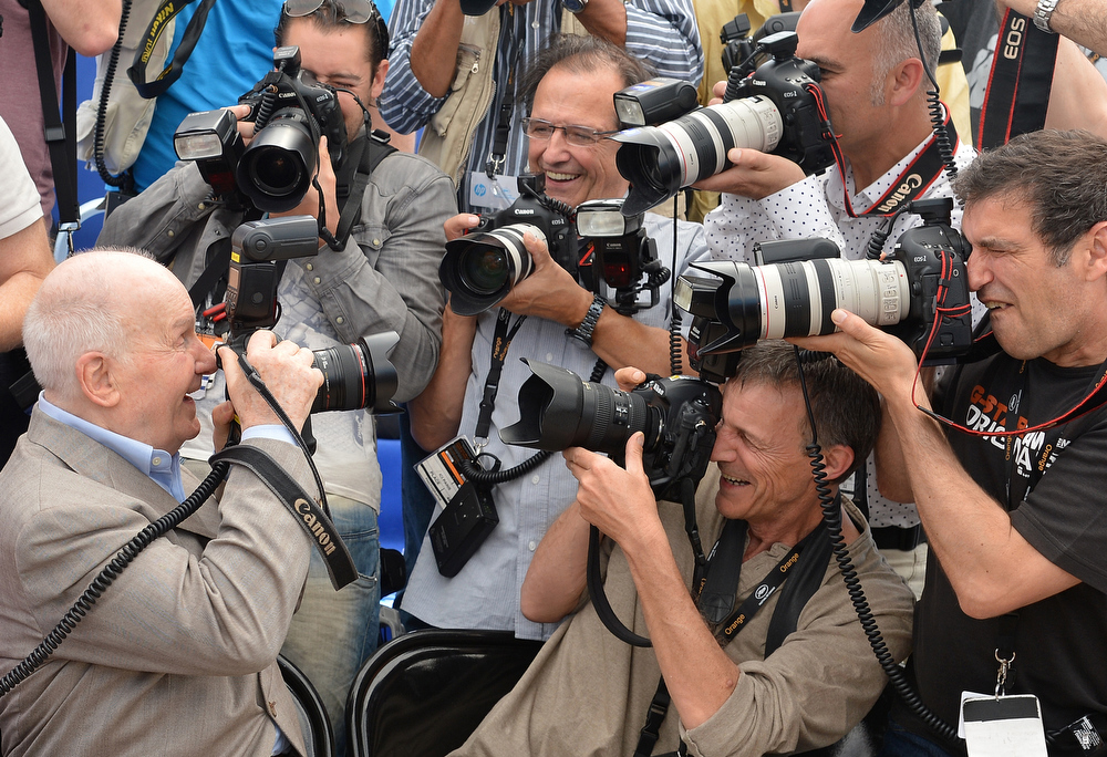 "Description of . French actor Michel Bouquet (L) takes pictures of photographers while posing during the photocall of ""Renoir\"" presented in the Un Certain Regard selection at the 65th Cannes film festival on May 26, 2012 in Cannes.    AFP PHOTO/ ALBERTO PIZZOLI"