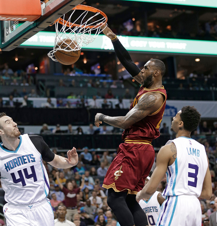. Cleveland Cavaliers\' LeBron James dunks against Charlotte Hornets\' Jeremy Lamb, right, and Frank Kaminsky, left, during the second half of an NBA basketball game in Charlotte, N.C., Friday, March 24, 2017. The Cavaliers won 112-105. (AP Photo/Chuck Burton)