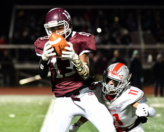 11/15/2019 Mike Orazzi rBristol Central's Tre Jones (13) hauls in a pass near Conard High School's Jack Tousignant (11) during Friday night's football game at BC. rr