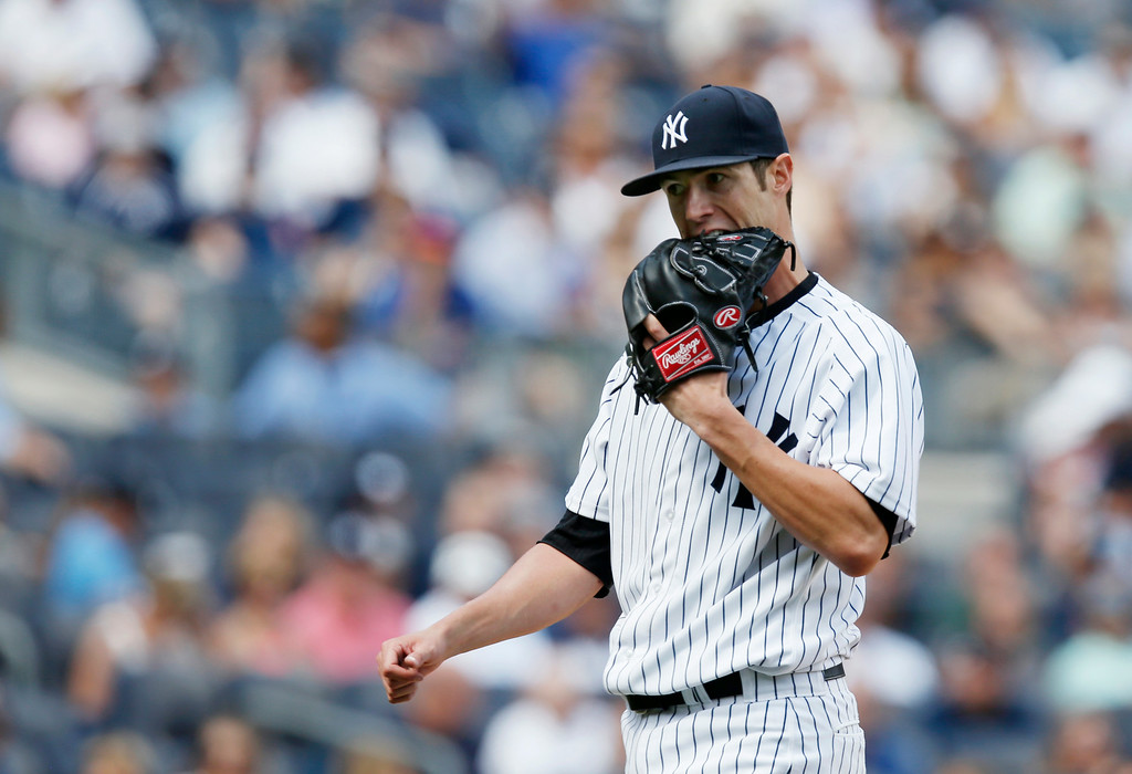 . New York Yankees starting pitcher Shane Greene bites his glove after issuing a walk in a 1-0 baseball game against the Detroit Tigers at Yankee Stadium in New York, Thursday, Aug. 7, 2014.  (AP Photo/Kathy Willens)