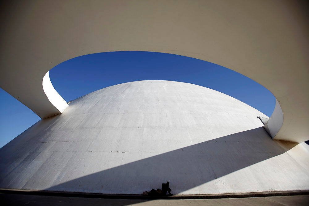 Description of . A homeless person sleeps outside the National Museum, designed by architect Oscar Niemeyer, in Brasilia in this April 7, 2010 photo. Niemeyer, a towering patriarch of modern architecture who shaped the look of modern Brazil and whose inventive, curved designs left their mark on cities worldwide, died late on December 5, 2012. He was 104. Niemeyer had been battling kidney ailments and pneumonia for nearly a month in a Rio de Janeiro hospital. His death was confirmed by a hospital spokesperson. REUTERS/Ricardo Moraes