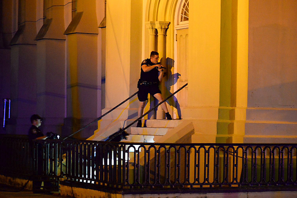 . Charleston police officers search for a shooting suspect outside the Emanuel AME Church, in downtown Charleston, S.C. on Wednesday, June 17, 2015.  A white man opened fire during a prayer meeting inside the historic black church killing several people. The shooter remained at large Thursday morning. (Matthew Fortner/The Post And Courier via AP)