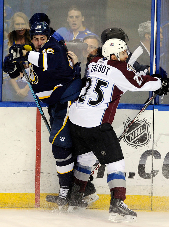 . Colorado Avalanche\'s Maxime Talbot (25) checks St. Louis Blues\' Roman Polak, of Czech Republic, during the third period of an NHL hockey game, Saturday, April 5, 2014, in St. Louis. (AP Photo/Bill Boyce)