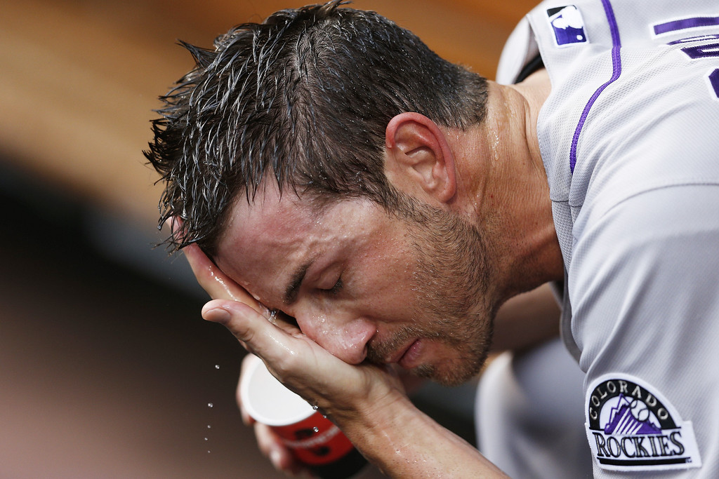 . Jon Garland #27 of the Colorado Rockies splashes water on his face while sitting in the dugout during the game against the Cincinnati Reds at Great American Ball Park on June 5, 2013 in Cincinnati, Ohio. (Photo by Joe Robbins/Getty Images)