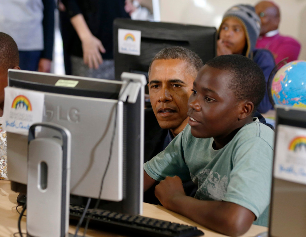 . U.S. President Barack Obama looks at a computer with a youth as he tours the Desmond Tutu HIV Foundation Youth Centre and takes part in a health event in Cape Town, South Africa on June 30, 2013.  REUTERS/Jason Reed