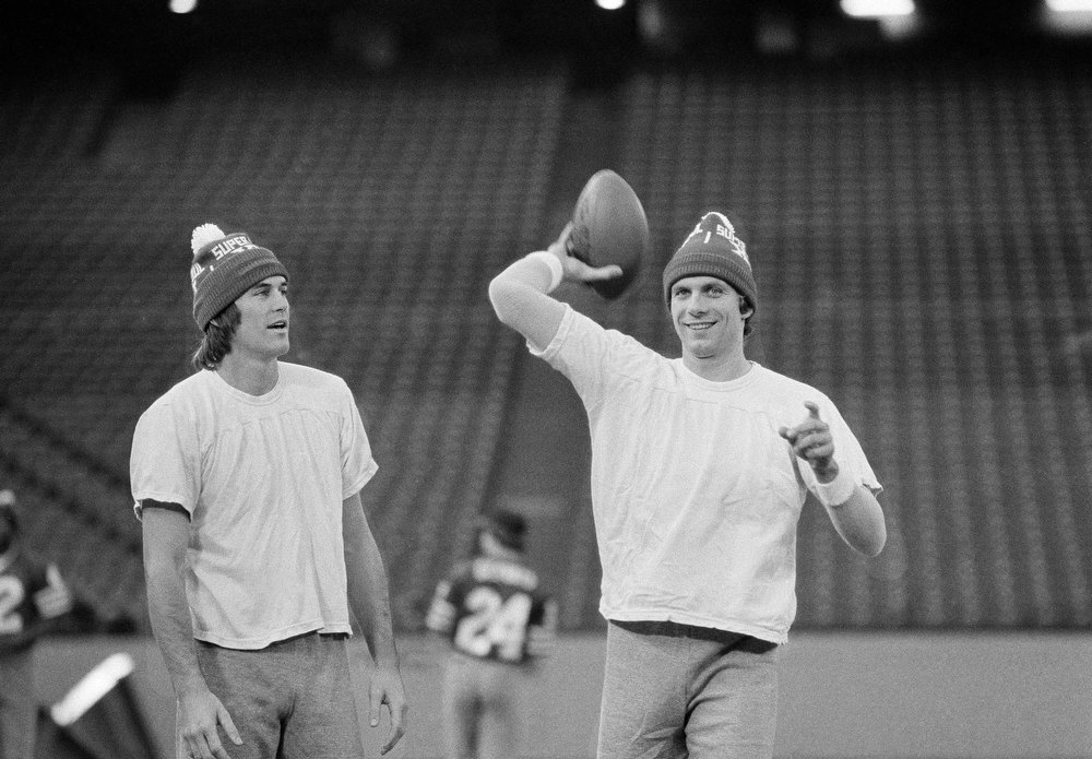 Description of . San Francisco 49ers Dwight Clark, left, and 49er quarterback Joe Montana wear their Super Bowl XVI hats as they go through a final workout in Pontiac\'s Silverdome, Michigan, on Saturday, Jan. 23, 1982, in preparation for Sunday\'s Super Bowl. (AP Photo)