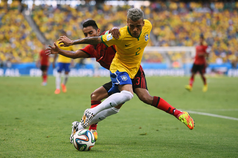 . Dani Alves of Brazil and Jose Juan Vazquez of Mexico battle for the ball during the 2014 FIFA World Cup Brazil Group A match between Brazil and Mexico at Castelao on June 17, 2014 in Fortaleza, Brazil.  (Photo by Laurence Griffiths/Getty Images)