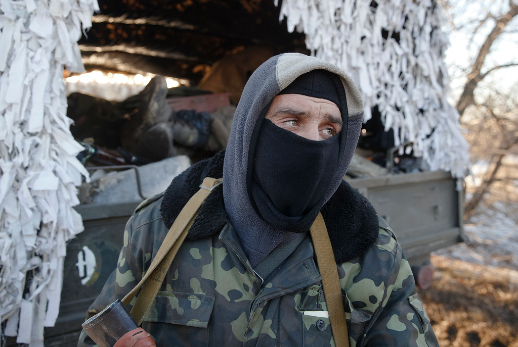 . An Ukrainian serviceman stands next to a broken down military vehicle outside Artemivsk, Ukraine, while pulling out of Debaltseve, Wednesday, Feb. 18, 2015. After weeks of relentless fighting, the embattled Ukrainian rail hub of Debaltseve fell Wednesday to Russia-backed separatists, who hoisted a flag in triumph over the town. The Ukrainian president confirmed that he had ordered troops to pull out and the rebels reported taking hundreds of soldiers captive.(AP Photo/Vadim Ghirda)