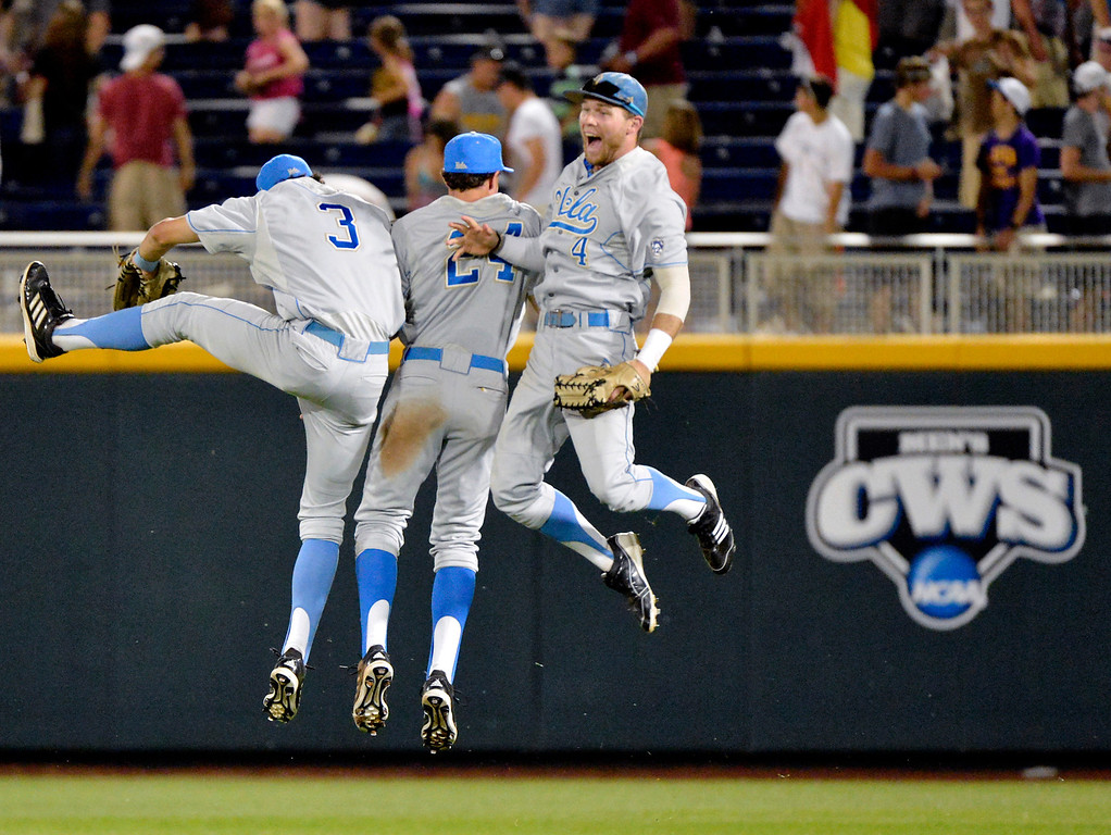 . UCLA players, from left, Christoph Bono, Brian Carroll and Eric Filia celebrate their 2-1 win over North Carolina State in an NCAA College World Series baseball game in Omaha, Neb., Tuesday, June 18, 2013. UCLA won 2-1. (AP Photo/Ted Kirk)