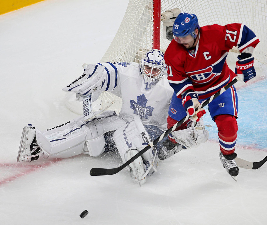 . Toronto Maple Leafs goaltender Ben Scrivens (L) makes a save against Montreal Canadiens\' Brian Gionta (21) during the first period of their NHL hockey game in Montreal January 19, 2013.  REUTERS/Christinne Muschi