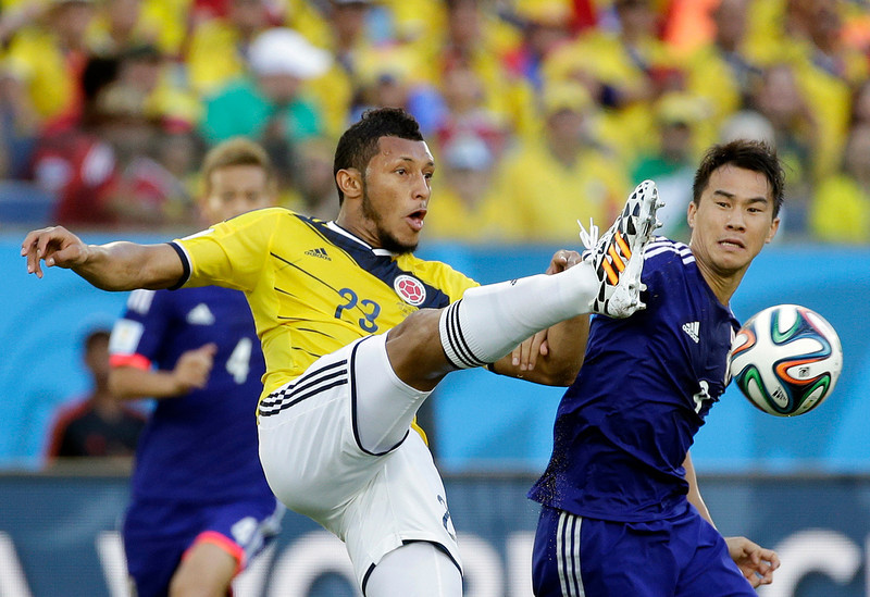 . Japan\'s Shinji Okazaki, right, fights for the ball with Colombia\'s Carlos Valdes during the group C World Cup soccer match between Japan and Colombia at the Arena Pantanal in Cuiaba, Brazil, Tuesday, June 24, 2014. (AP Photo/Felipe Dana)