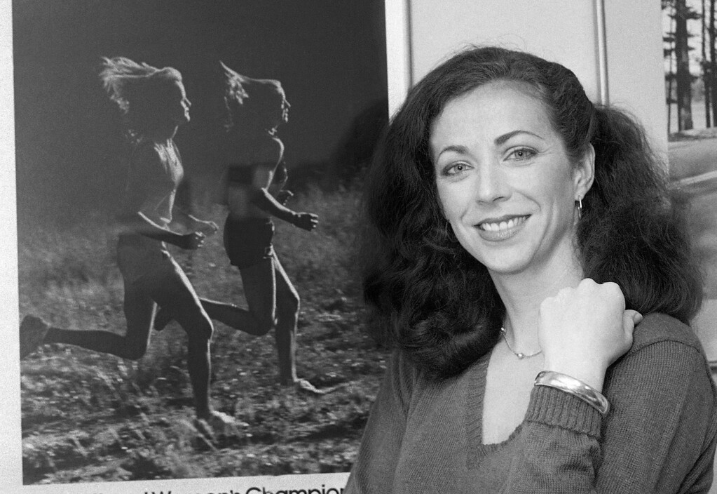 . FILE - In this May 22, 1980 file photo, pioneer woman marathoner Kathrine Switzer stands in her New York office. In 1967, Switzer became the first woman to run with an official bib number in the Boston Marathon. A new film that captures much of the Boston Marathon\'s colorful history premieres Saturday, April 15, 2017, in conjunction with the 121st running of the race on Monday. (AP Photo/Suzanne Vlamis, File)