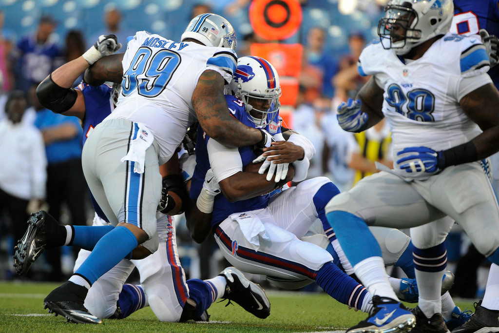 . Detroit Lions defensive tackle C.J. Mosley (99) brings down Buffalo Bills quarterback EJ Manuel (3) during the first half of a preseason NFL football game, Thursday, Aug. 28, 2014, in Orchard Park, N.Y. (AP Photo/Gary Wiepert)