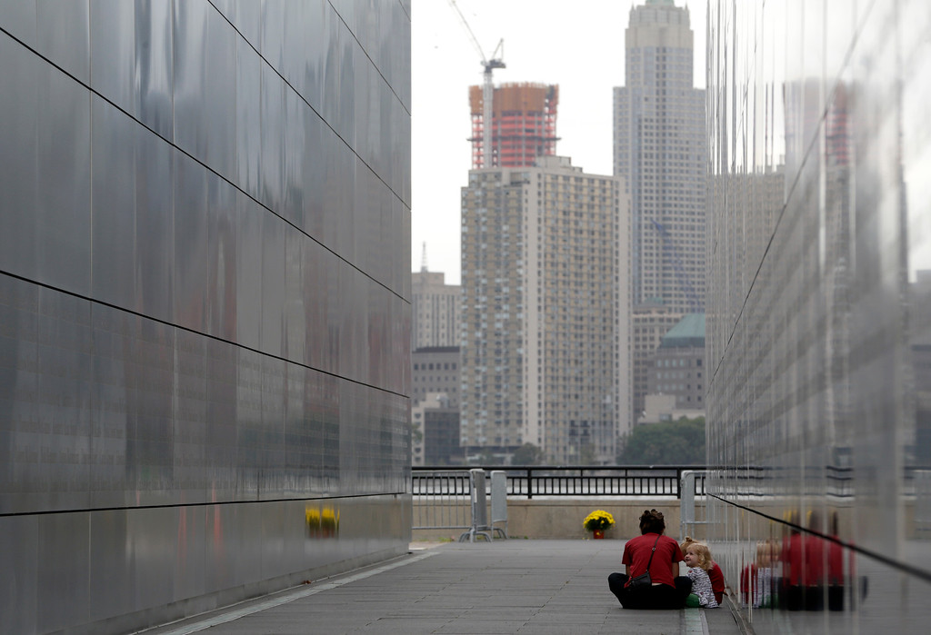 . Tammi Powlen-Beck, of Bayonne, N.J., sits with her daughters Lauren Beck, 1, front right, and Jenna Beck, 3, at the Empty Sky Memorial at Liberty State Park, Thursday, Sept. 11, 2014, in Jersey City, N.J. (AP Photo/Julio Cortez)
