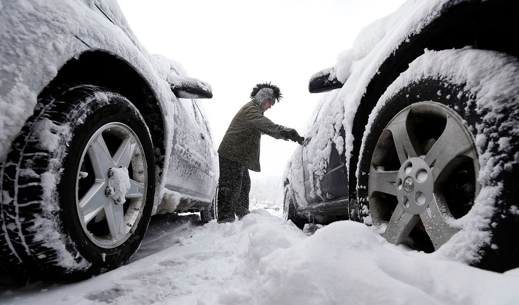 . Noah Nichols, of Des Moines, Iowa, cleans snow off his car, Thursday, Dec. 20, 2012, in Des Moines, Iowa. The first widespread snowstorm of the season began a slow crawl across the Midwest on Thursday with some areas receiving as much as 15 inches of snow. (AP Photo/Charlie Neibergall)
