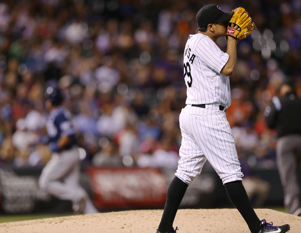 . Colorado Rockies starting pitcher Jorge De La Rosa, front, reacts after giving up a solo home run to San Diego Padres\' Tommy Medica, back, to lead off the fifth inning of a baseball game in Denver on Saturday, Sept. 6, 2014. (AP Photo/David Zalubowski)