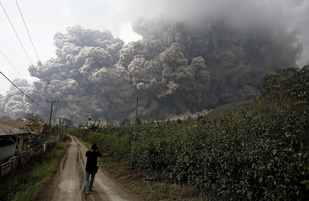 . An Indonesian journalist looks at the mounth Sinabung spewing volcanic materials in Karo, North Sumatra, Indonesia, 01 February 2014. At least 14 people were killed when a volcano on the Indonesian island of Sumatra spewed lava and hot gas, an aid worker said.  EPA/CHAIRALY