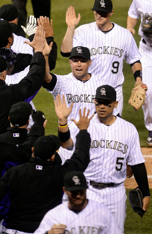. DENVER, CO - APRIL 5:  DJ LeMahieu (9) Michael Cuddyer (3) and Carlos Gonzalez (5) celebrated the win Saturday night. The Colorado Rockies defeated the Arizona Diamondbacks 9-4 Saturday night, April 5, 2014 in Denver. (Photo by Karl Gehring/The Denver Post)