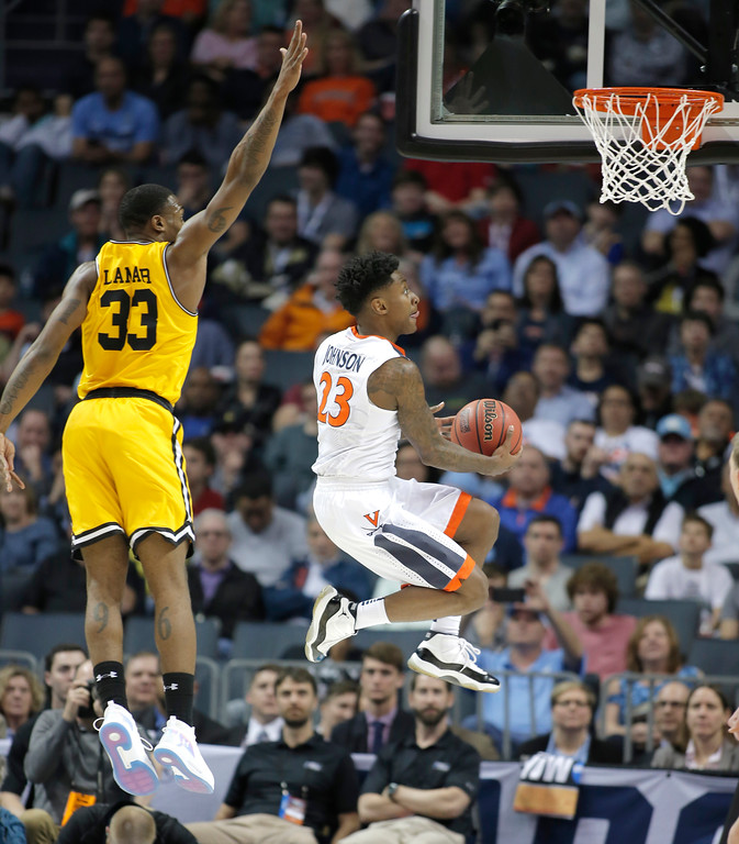 . Virginia\'s Nigel Johnson (23) drives past UMBC\'s Arkel Lamar (33) during the first half of a first-round game in the NCAA men\'s college basketball tournament in Charlotte, N.C., Friday, March 16, 2018. (AP Photo/Bob Leverone)