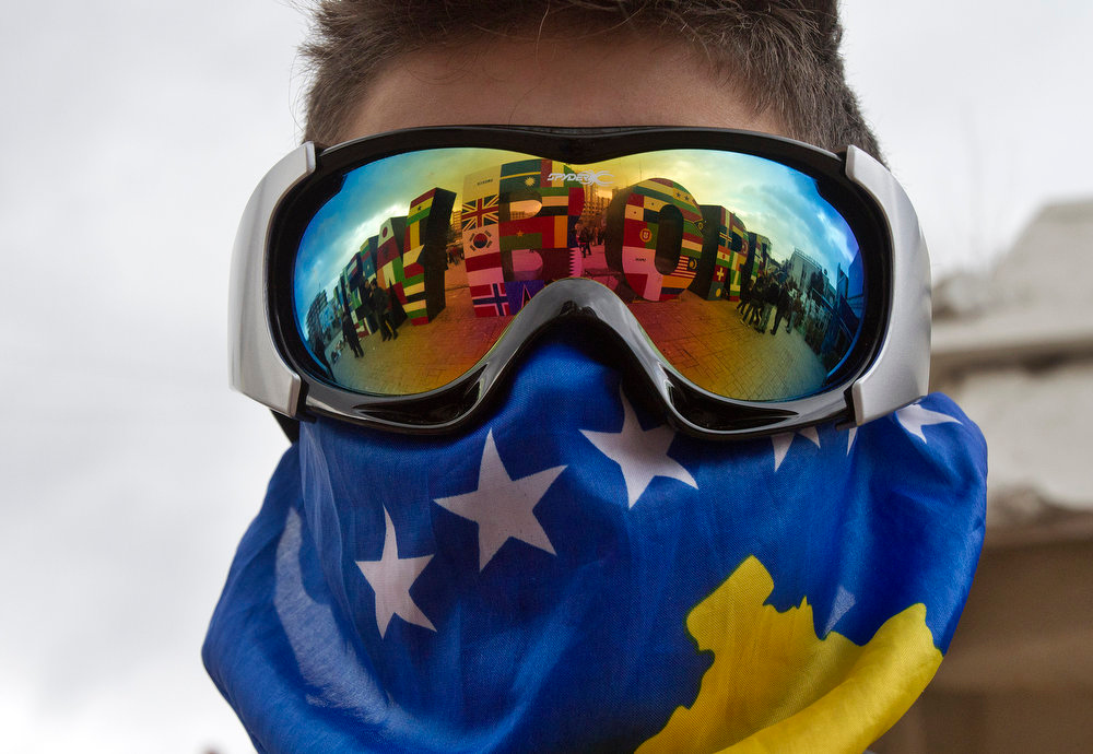 Description of . A Kosovo Albanian youth wearing ski goggles and a Kosovo flag stands near the