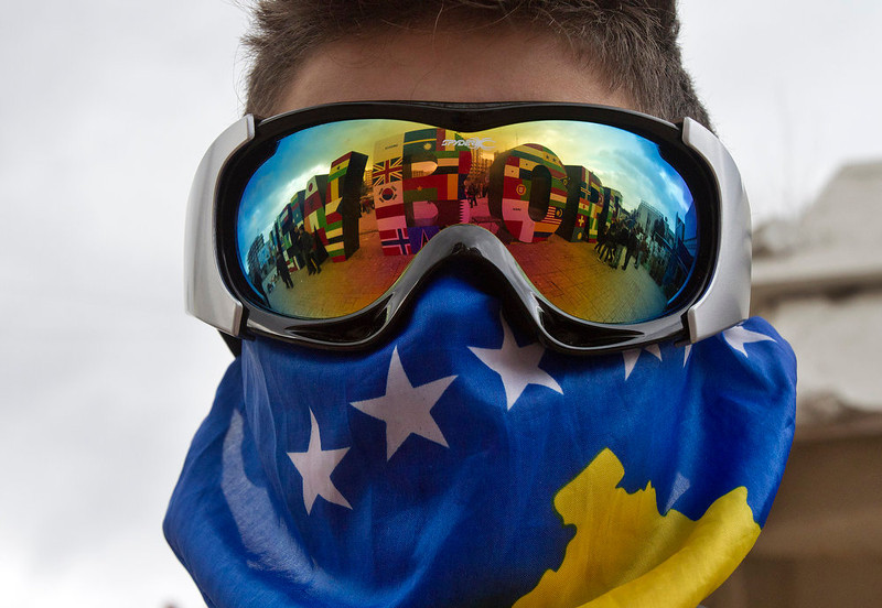 ". A Kosovo Albanian youth wearing ski goggles and a Kosovo flag stands near the ""NEWBORN\"" monument painted with flags of the countries that have recognized Kosovo\'s independence marking the 5th anniversary since Kosovo seceded from Serbia in capital Pristina on Sunday, Feb. 17, 2013. Serbia rejects Kosovo independence. (AP Photo/Visar Kryeziu)"