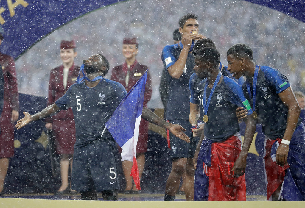 . France\'s Samuel Umtiti, left, bites his winners medal after the final match between France and Croatia at the 2018 soccer World Cup in the Luzhniki Stadium in Moscow, Russia, Sunday, July 15, 2018. France won the final 4-2. (AP Photo/Matthias Schrader)