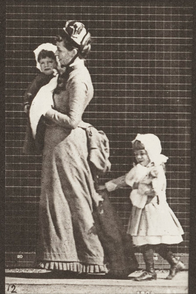 Woman walking, carrying a child and turning around
