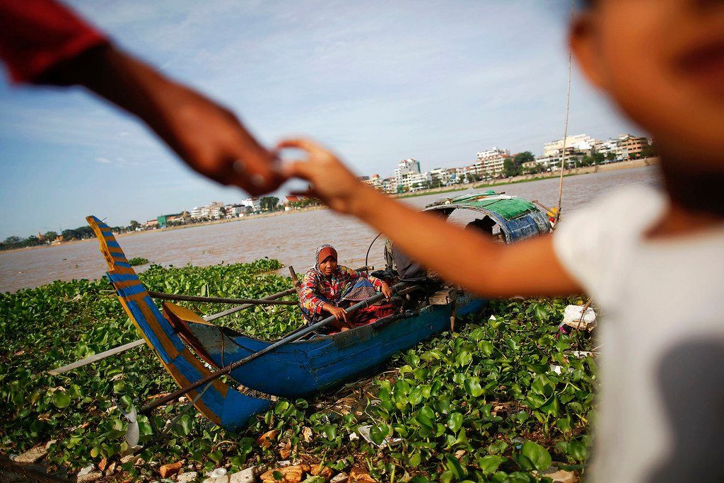 . An ethnic Cham Muslim woman sits on her boat on the banks of Tonle Sap river in Phnom Penh July 30, 2013. About 100 ethnic Cham families, made up of nomads and fishermen without houses or land who arrived at the Cambodian capital in search of better lives, live on their small boats on a peninsula where the Mekong and Tonle Sap rivers meet, just opposite the city\'s centre. The community has been forced to move several times from their locations in Phnom Penh as the land becomes more valuable. They fear that their current home, just behind a new luxurious hotel under construction at the Chroy Changva district is only temporary and that they would have to move again soon.   REUTERS/Damir Sagolj