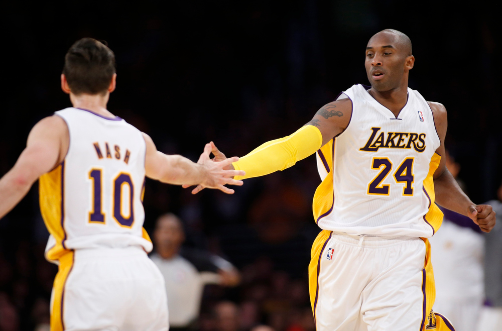 . Los Angeles Lakers\' Kobe Bryant (R) and Steve Nash (L) slap hands after Bryant assisted Nash on a three-pointer during the first half of their NBA basketball game against the Denver Nuggets in Los Angeles January 6, 2013. REUTERS/Danny Moloshok