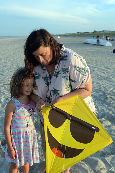 6 year old Nancy Cross watches as her mom Karen makes some adjustments to Her kite at the Kites and Castles event on Lavallette Beach, in. Lavallette, NJ on 08/01/2019.