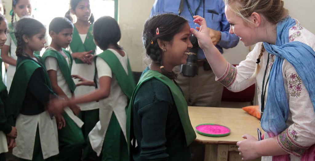 . Amber Zeise, of Capiotla applies a colored powder tilak on the forehead of a young Pardada Pardadi School student on March 26 in Anupshahr, India. Zeise and her Mount Madonna School classmates are on a 2-week learning adventure in India.