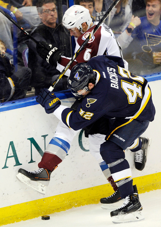 . St. Louis Blues\' David Backes (42) checks Colorado Avalanche\'s Erik Johnson (6) during the third period of an NHL hockey game Saturday, April 5, 2014, in St. Louis. (AP Photo/Bill Boyce)