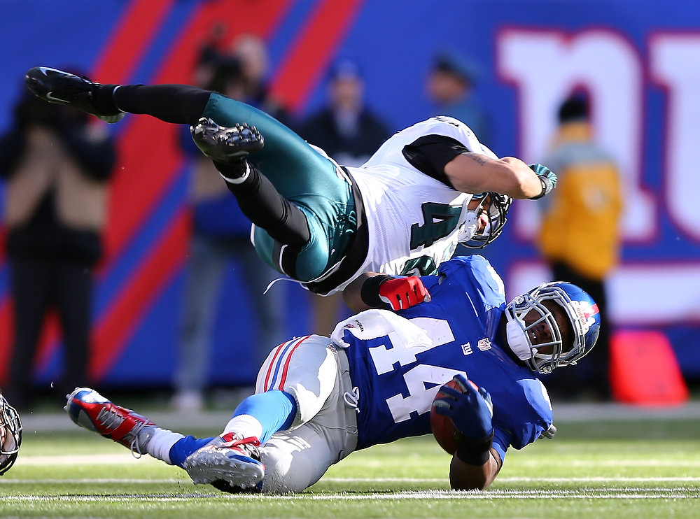 Description of . Ahmad Bradshaw #44 of the New York Giants is tackled by Kurt Coleman #42 of the Philadelphia Eagles defends  at MetLife Stadium on December 30, 2012 in East Rutherford, New Jersey.  (Photo by Elsa/Getty Images)
