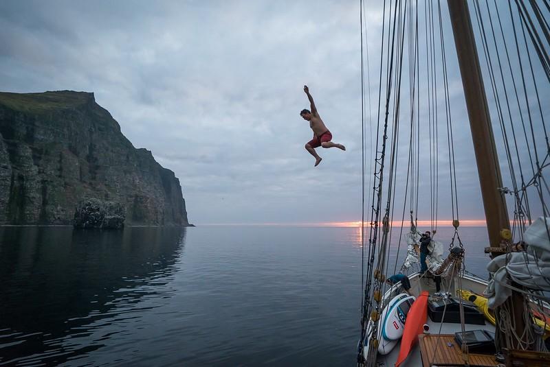 Chris Burkard jumping off Arktika. Hornstrandir, Iceland.