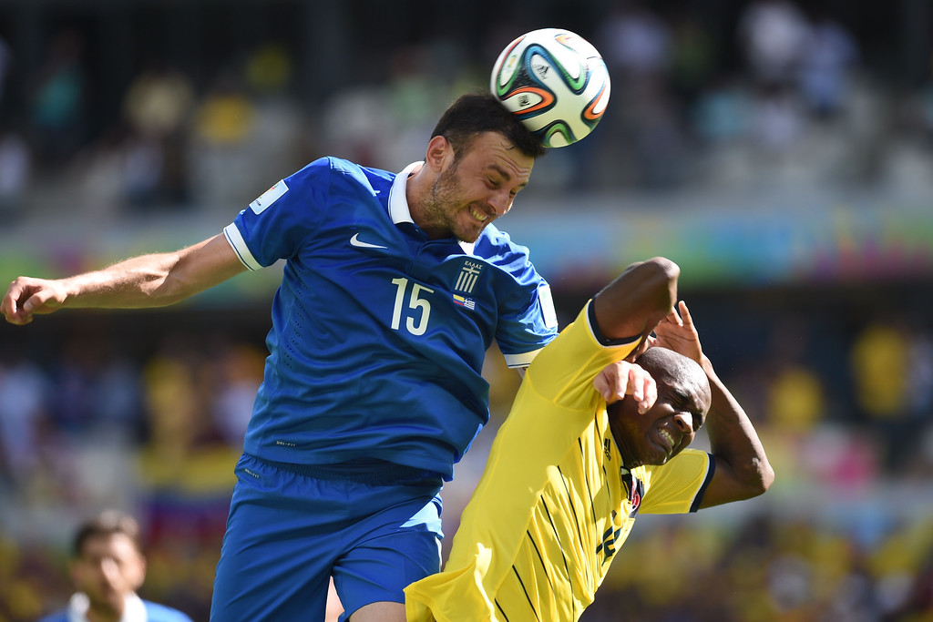 . Colombia\'s forward Victor Ibarbo (R) is challenged by Greece\'s defender Vasilis Torosidis during a group C football match between Colombia and Greece at the Mineirao Arena in Belo Horizonte during the 2014 FIFA World Cup on June 14, 2014.    AFP PHOTO / PEDRO UGARTE