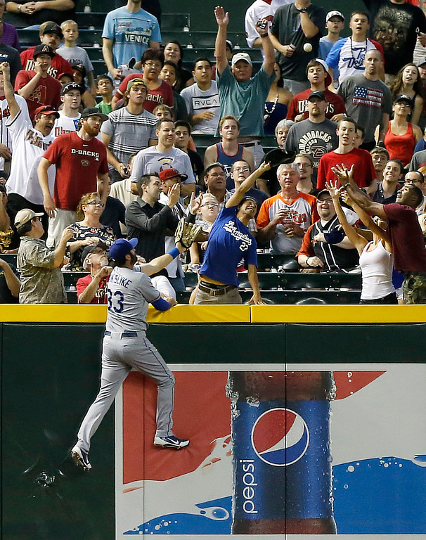 . Los Angeles Dodgers\' Scott Van Slyke can\'t reach a home run hit by Arizona Diamondbacks\' Aaron Hill during the first inning of a baseball game, Wednesday, July 10, 2013, in Phoenix. (AP Photo/Matt York)