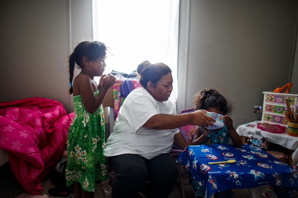 . Clarissa Taitano helps her 3-year-old daughter I\'Yannah Jackson eat her breakfast as her older daughter, A\'Riyah Jackson, 5, looks on in their mobile home on May 24, 2013, in San Jose. The family recently moved to their mobile home after living in a Santa Clara motel for 64 days. (Dai Sugano/Bay Area News Group)