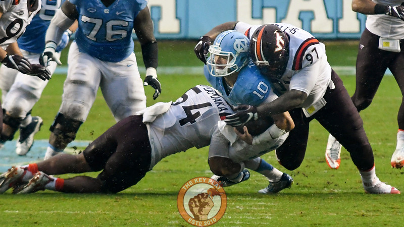 Virginia Tech defensive tackle Tim Settle (97) and linebacker Andrew Motuapuaka (54) bring down North Carolina quarterback Mitch Trubisky (10). (Michael Shroyer/ TheKeyPlay.com)