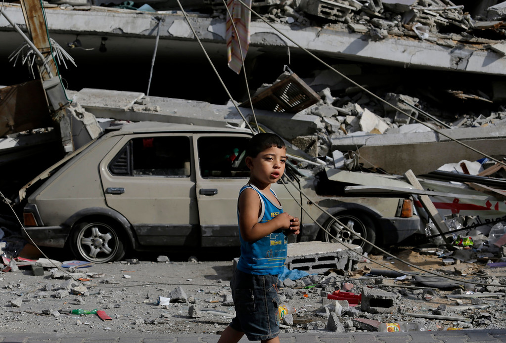 . Palestinian Abdel Aziz Jendiyah, 4, walks past a six-story building, destroyed by an Israeli strike earlier during the war, adjacent to his family house, in the Sabra neighborhood of Gaza City, northern Gaza Strip, Thursday, July 31, 2014. The Jendiyah family building houses 21 members of the extended family, and now with several rooms destroyed, they try to go about their lives, without electricity and without running water for several hours a day. (AP Photo/Lefteris Pitarakis)