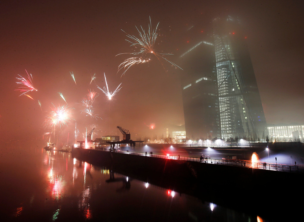 . Fireworks explode during New Years celebrations near the new headquarters of the European Central Bank in Frankfurt, Germany, Thursday, Jan. 1, 2015. (AP Photo/Michael Probst)