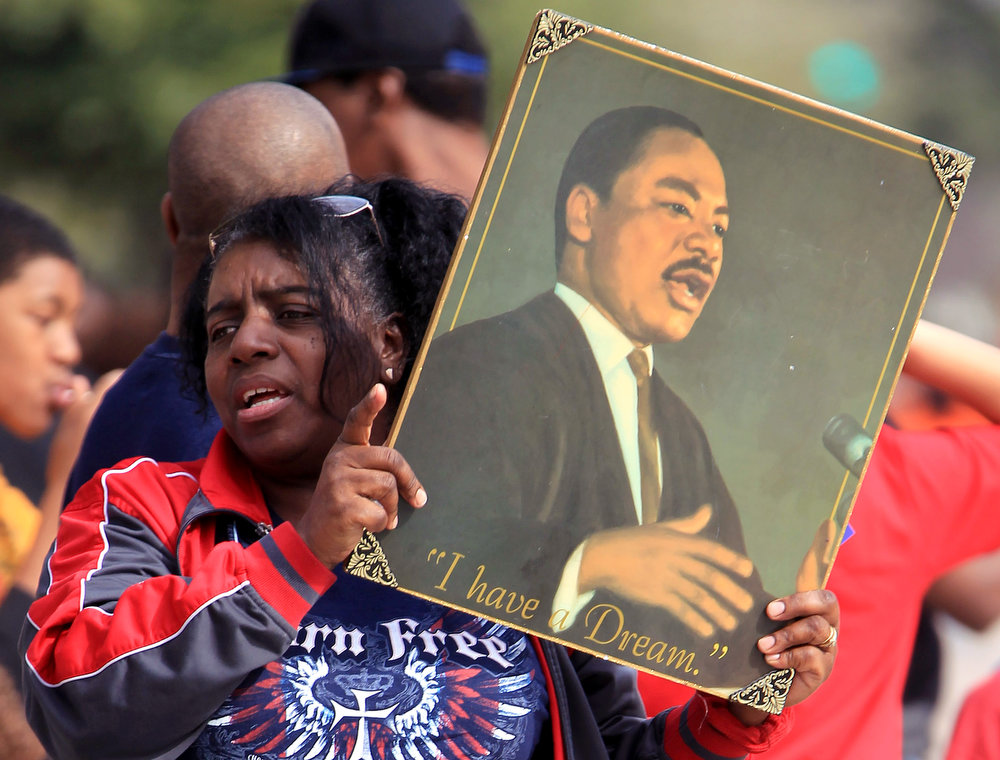 Description of . Marilyn Smith holds up a painting of Rev. Martin Luther King made by her godson during the 19th Annual MLK Grande Parade by the MLK Parade Foundation in Houston, Monday, Jan. 21, 2013. (AP Photo/Houston Chronicle, Karen Warren)