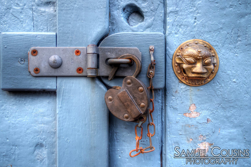 A padlock and decoration on the door of a local workshop.
